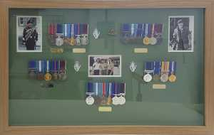 Family medal collection framed with badges and photographs